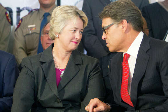 Mayor Annise Parker, left, and Governor Rick Perry talk before a news conference at City Hall announcing an Anti-human trafficking campaign, Tuesday, June 3, 2014, in Houston.