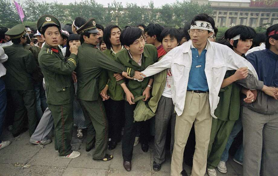 Students and police link arms to keep crowds of people, many of these relatives of strikers, from Tiananmen Square, where students have been on hunger strike since Saturday, Thursday, May 18, 1989, Beijing, China. Photo: Sadayuki Mikami, AP / 1989 AP