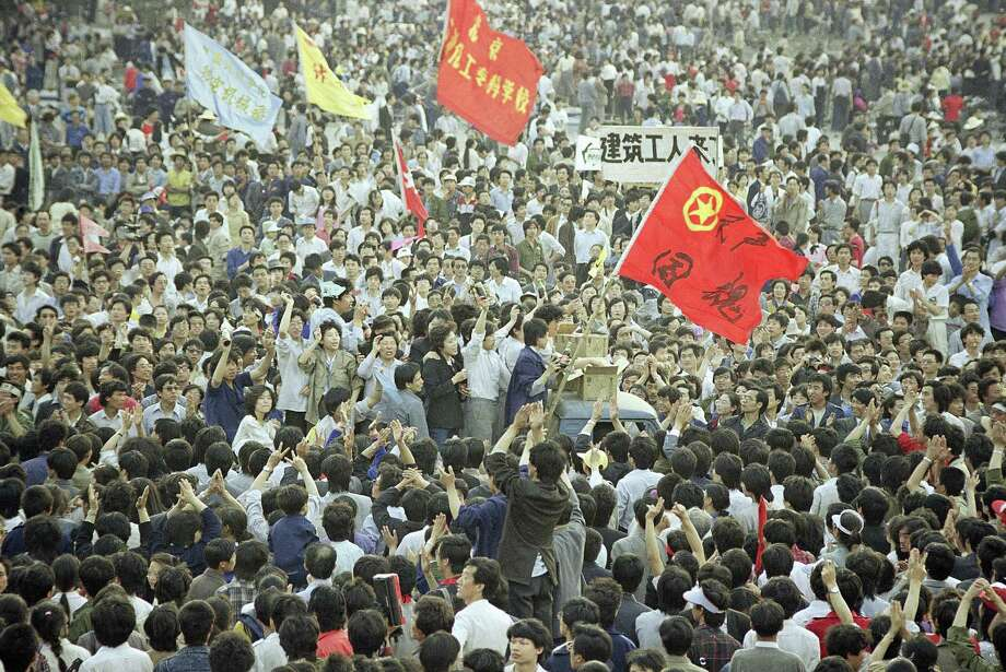 A truck is almost buried in people as it makes its way through the crowd of thousands gathered in Tiananmen Square for a pro-democracy rally, Wednesday, May 17, 1989, Beijing, China. Photo: Sadayuki Mikami, ASSOCIATED PRESS / AP1989