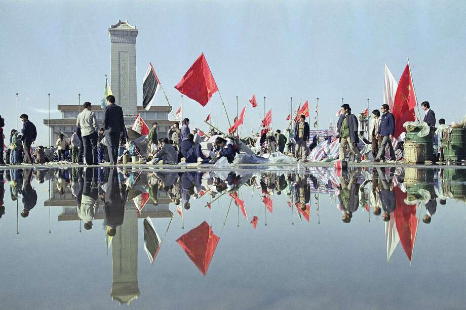 Morning activity in Beijing's Tiananmen Square is reflected in the wet pavement, May 24,1989, following a downpour the night before. In the background are the Martyrs monument and beyond that, Mao's mausoleum. Photo: Mark Avery, AP / 1989 AP