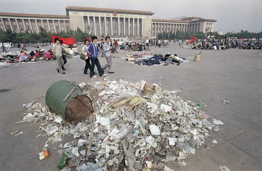 Striking Beijing university students stroll past piles of garbage in Tiananmen Square, Beijing, May 27, 1989, where they have camped in a protest for political reform for two weeks. Photo: Jeff Widener, AP / 1989 AP