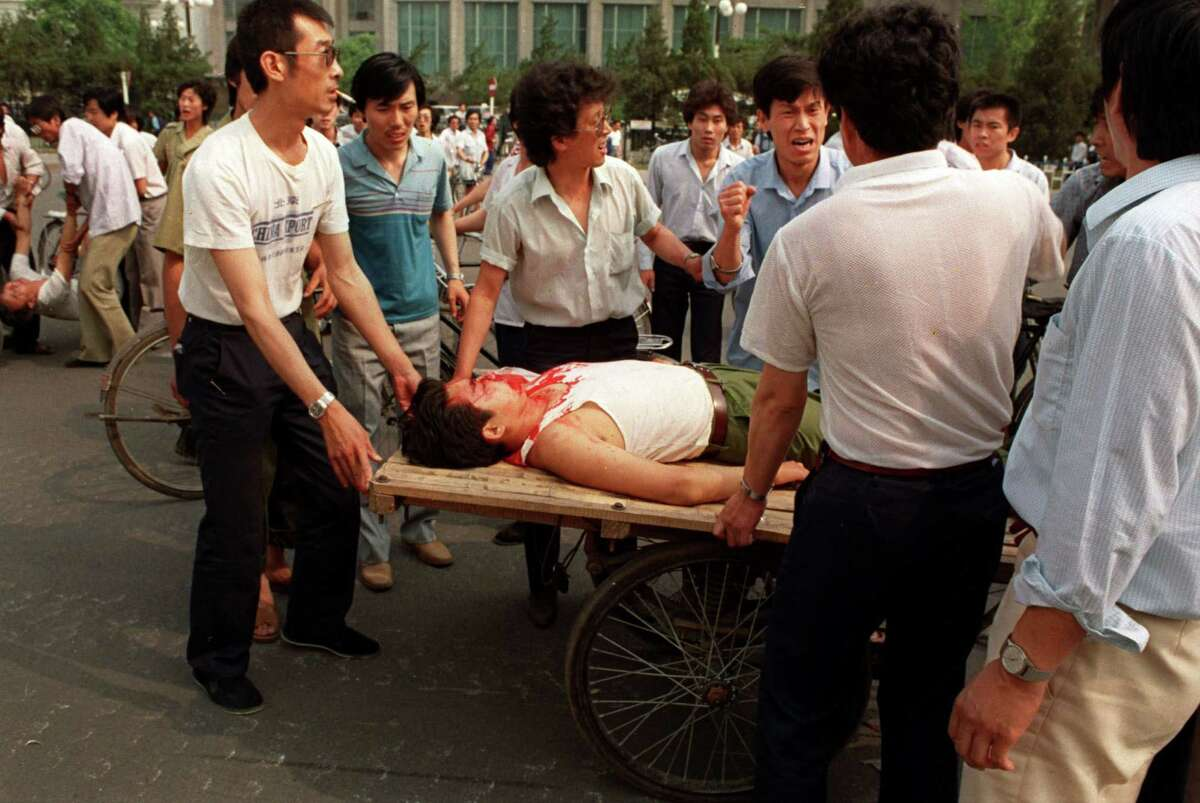Local residents loaded the wounded people on a rickshaw flatbed shortly after PLA soldiers opened fire on a crowd in this June 4, 1989 photo. On Friday, it will be 25 years since the military assault that killed hundreds and ended seven weeks of protests centered on Tiananmen Square.