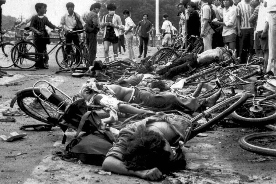 The bodies of dead civilians lie among mangled bicycles near Beijing's Tiananmen Square early June 4, 1989.  Tanks and soldiers stormed the area overnight, bringing a violent end to student demonstrations for democratic reform in China. Photo: Anonymous, AP / 1989 AP
