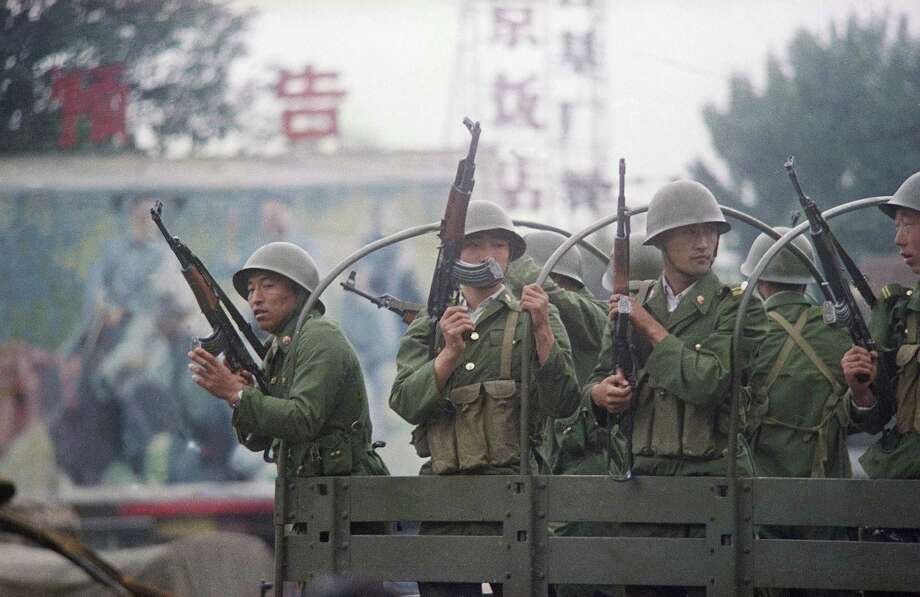 Chinese troops keep a sharp eye out as their truck makes a momentary stop on Changan Blvd., Wednesday, June 7, 1989, Beijing, China. Photo: Terril Jones, AP / 1989 AP