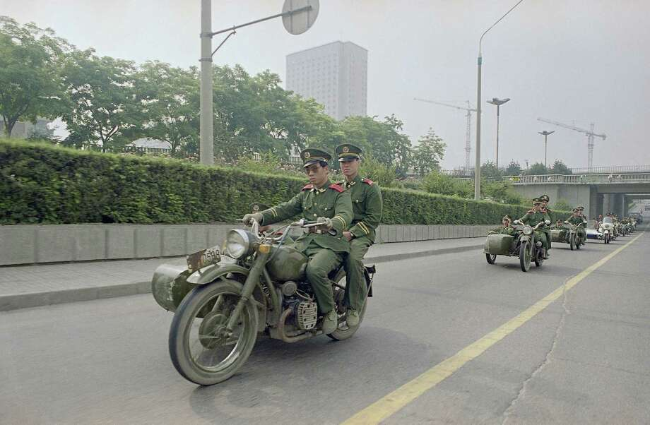PLA (People's Liberation Army) troops from the Beijing garrison, patrol the streets on motorcycles, May 31, 1989 in Beijing. Parts of the city have been under martial law since May 20 in an effort to break up the student protests in Tiananmen Square. Photo: Liu Heung Shing, AP / 1989 AP