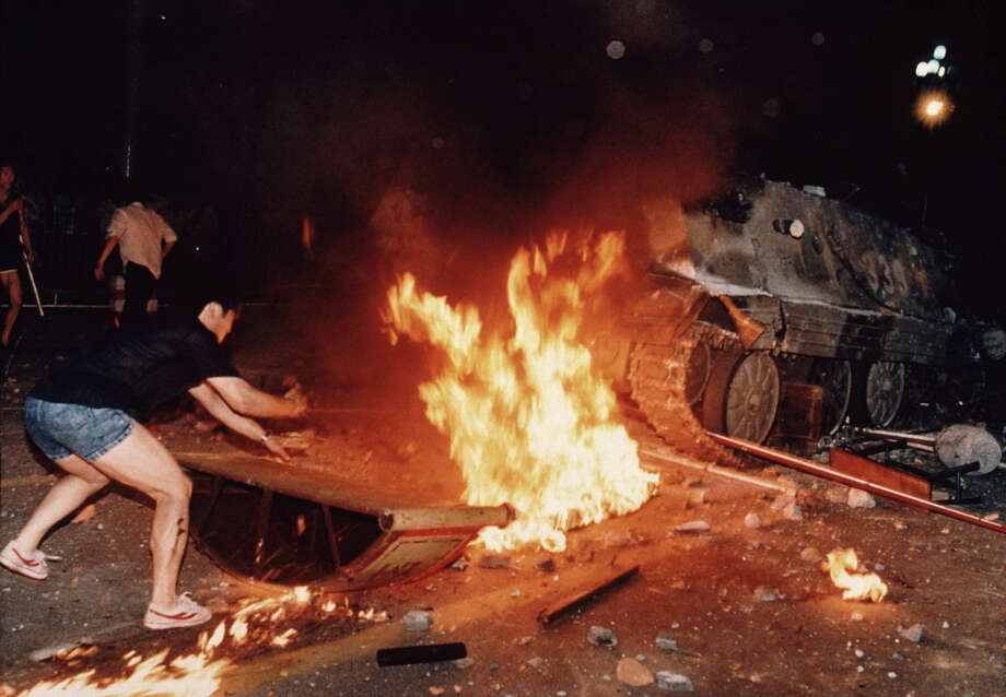 A student protester puts barricades in the path of an already burning armored personnel carrier that rammed through student lines during an army attack on anti-government demonstrators in Beijing's Tiananmen Square, early June 4, 1989. A govenment soldier who escaped the armored vehicle was killed by demonstrators. Pro-democracy protesters occupied the square for seven weeks; hundreds died in the early hours of June 4, 1989 when troops shot their way through Beijing's streets to retake the square. Photo: JEFF WIDENER, ASSOCIATED PRESS / AP1989