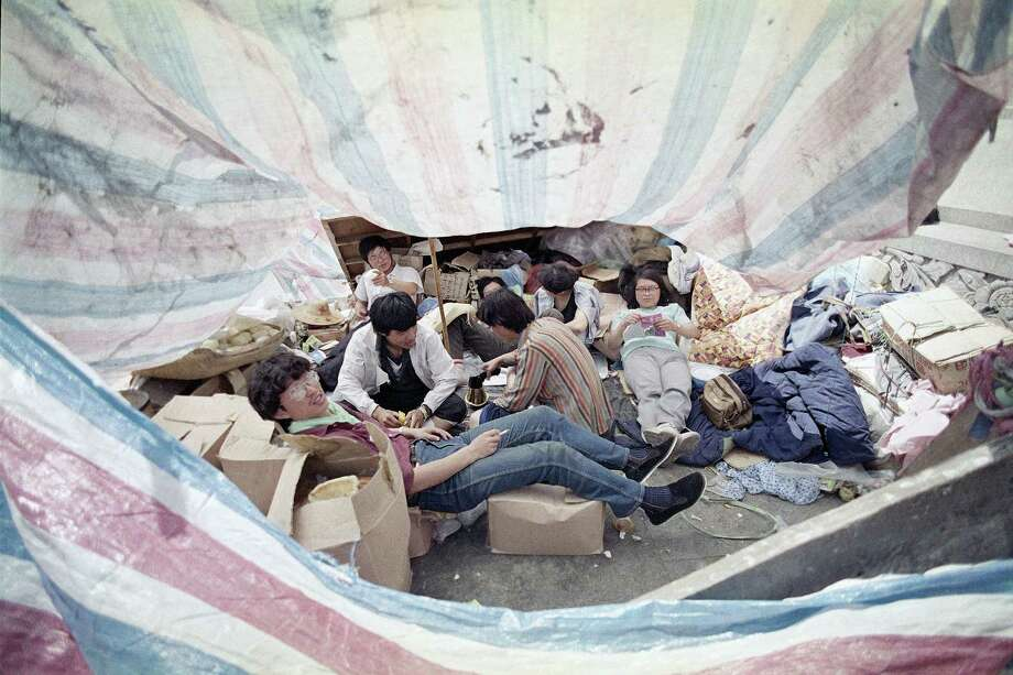 Students occupying Tiananmen Square in Beijing relax in the shade of the of their tent during a hot afternoon, May 26, 1989. They have camped in the square during a demonstration for democracy for 13 days. Photo: Jeff Widener, AP / 1989 AP