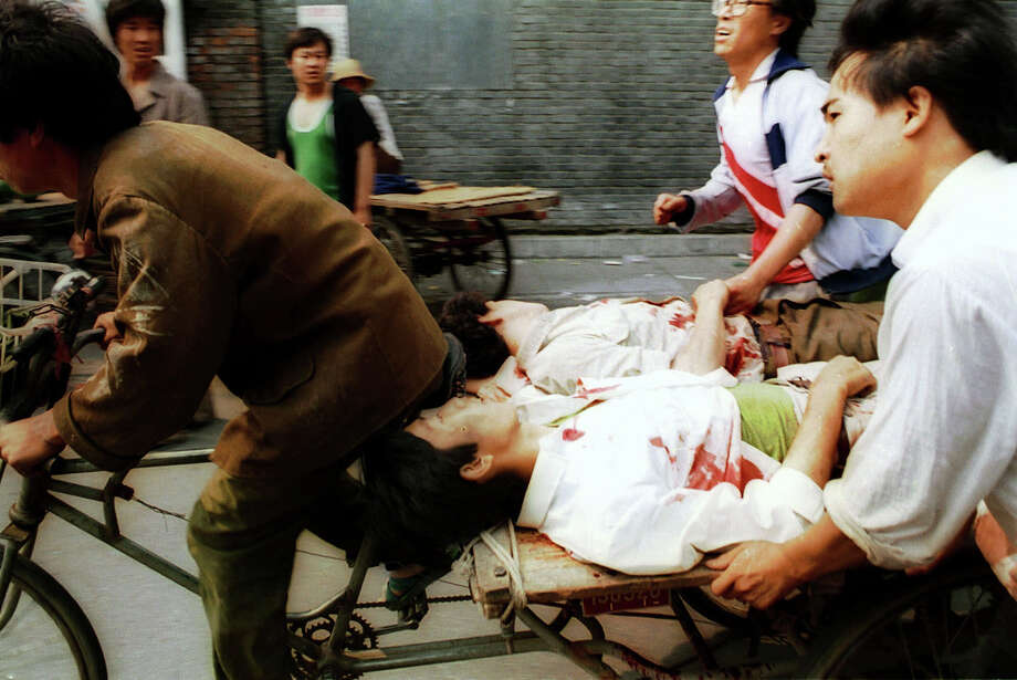 A rickshaw driver fiecely peddles the wounded people, with the help of bystanders, to a nearby hospital Sunday, June 4, 1989. PLA soldiers again fired hundreds of rounds towards angry crowds gathered outside Tiananmen Square at noon. Photo: LIU HEUNG SHING, AP / 1989 AP