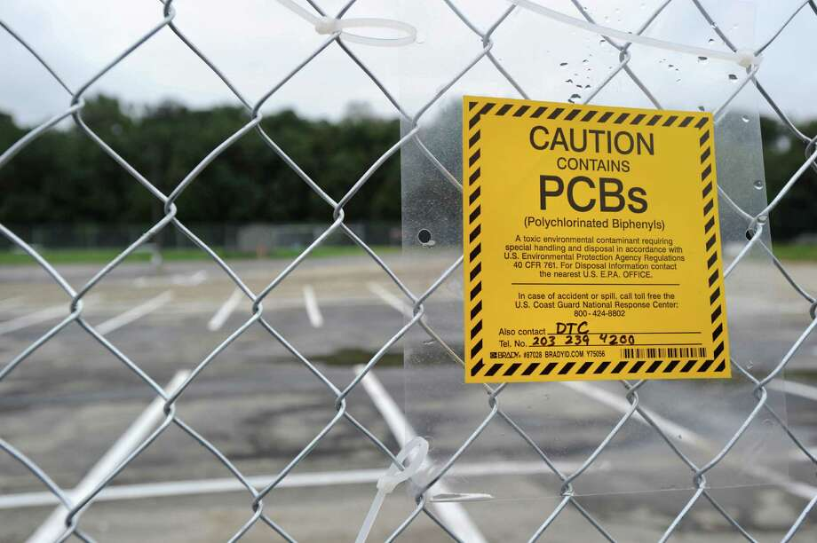 A sign attached to a fence in the western parking lot at Greenwich High School Sept. 20, 2011, warns of PCBs unearthed during the school's project to build a new auditorium and music space. Photo: Bob Luckey / Greenwich Time