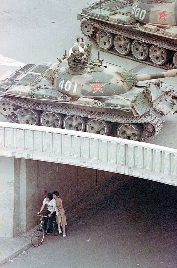A Chinese couple on a bicycle take cover at an underpass as tanks deploy overhead in eastern Beijing, China, June 5, 1989.  Chinese troops crushed a pro-democracy demonstration held by students and other demanding democratic reform in Tiananmen Square on June 4. Photo: LIU HEUNG SHING, AP / 1989 AP