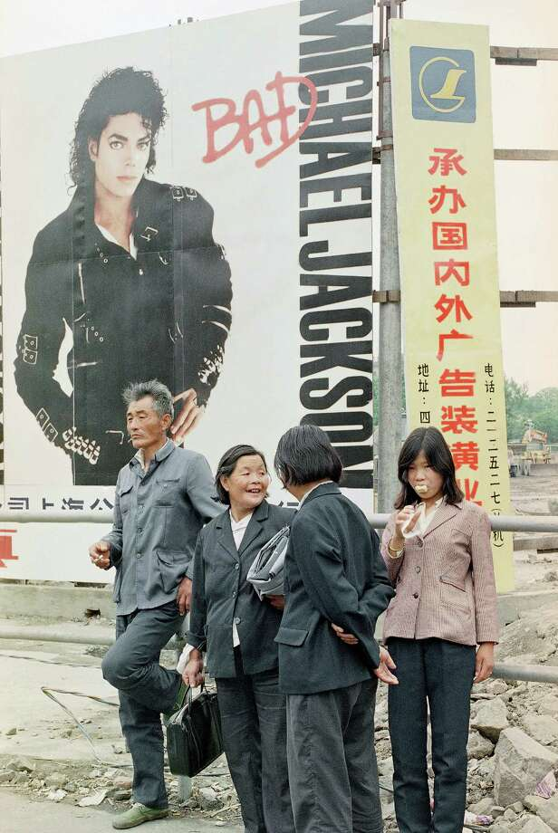A Chinese family pauses in front of a huge promotion poster of Michael Jackson at Peoples Square, Sunday, June 11, 1989, Shanghai, China. The city is back to normal with a usual huge crowd of Sunday shoppers bustling up and down the streets. Photo: MIS, ASSOCIATED PRESS / AP1989