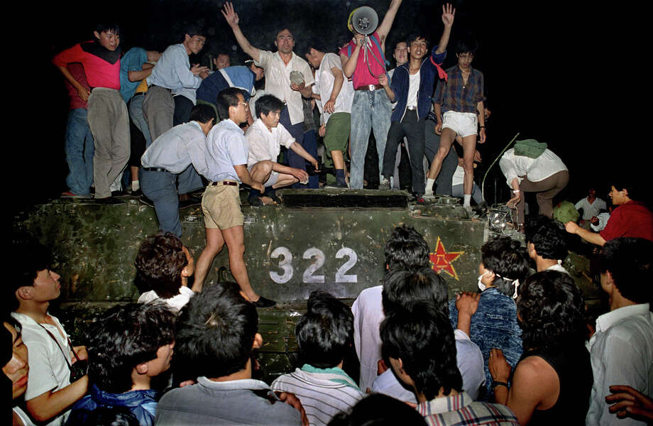 Civilians hold rocks as they stand on a government armored vehicle near Chang'an Boulevard in Beijing, early June 4, 1989. Violence escalated between pro-democracy protesters and Chinese troops, leaving hundreds dead overnight. Photo: Jeff Widener, AP / 1989 AP