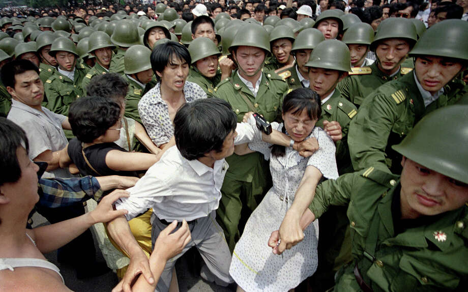A young woman is caught between civilians and Chinese soldiers, who were trying to remove her from an assembly near the Great Hall of the People in Beijing, June 3, 1989. Pro-democracy protesters had been occupying Tiananmen Square for weeks. Photo: Jeff Widener, ASSOCIATED PRESS / AP1989