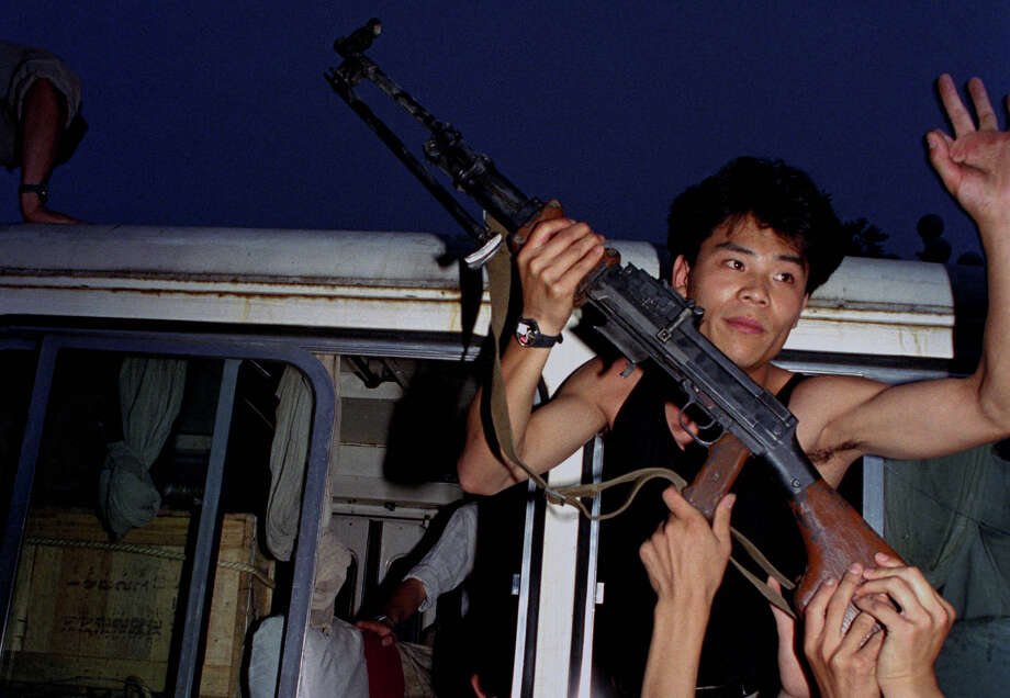 An anti-government protester in Beijing holds a rifle in a bus window, June 3, 1989. Pro-democracy protesters had been occupying Tiananmen Square for weeks; hundreds died that night and the following morning in clashes with Chinese troops. Photo: Jeff Widener, AP / AP