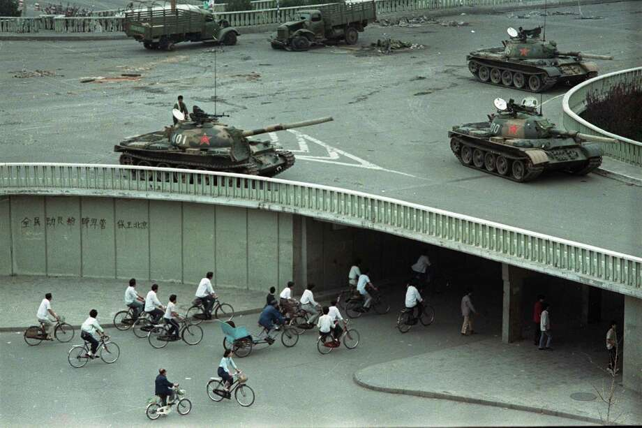 "FILE - In this June 6, 1989 file photo, bicycle commuters, sparse in numbers, pass through a tunnel as above on the overpass military tanks are positioned in Beijing, two days after the Tiananmen Square massacre on Tuesday morning, June 6, 1989. The slogan on the wall at left reads: ""Strike down martial law."" A quarter century after the Communist Party's attack on demonstrations centered on Tiananmen Square on June 4, 1989, the ruling party prohibits public discussion and 1989 is banned from textbooks and Chinese websites. Photo: Vincent Yu, AP / AP"