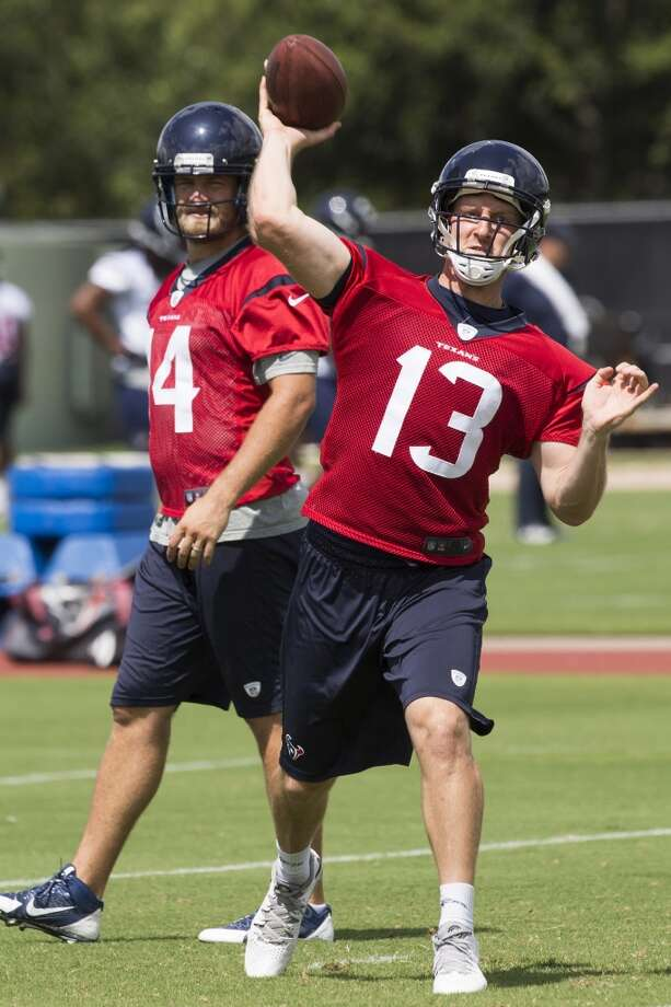 Texans quarterback T.J. Yates (13) throws a pass as Ryan Fitzpatrick walks past. Photo: Brett Coomer, Houston Chronicle