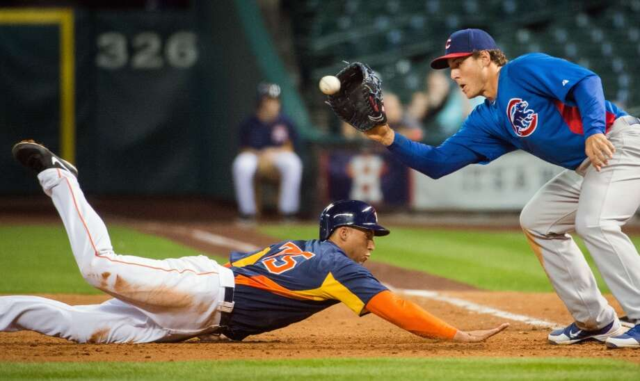Springer dives back to first ahead of the tag from Cubs first baseman Anthony Rizzo during an exhibition game at Minute Maid Park on March 29, 2013. Photo: Smiley N. Pool, Houston Chronicle