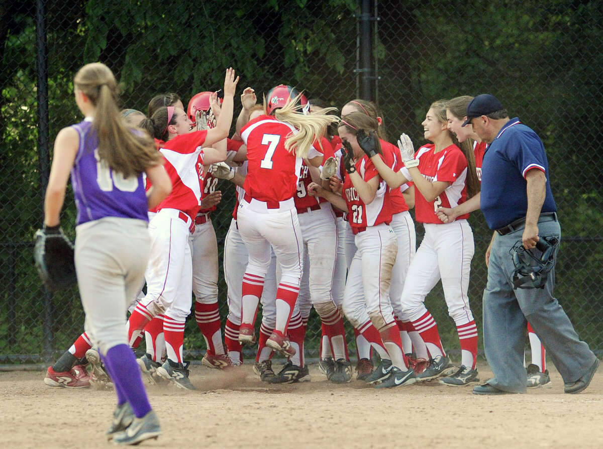 At center, Rebecca DeCarlo (#7) of Greenwich is mobbed by her teammates while touching home plate after DeCarlo hit the walk-off game-winning home run in the bottom of the 8th inning to defeat rival Westhill 3-2 in the Class LL softball game between Greenwich High School and Westhill High School at Greenwich, Tuesday, June 3, 2014.