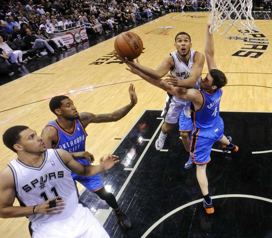 San Antonio Spurs' Cory Joseph shoots over Oklahoma City Thunder's Nick Collison as San Antonio Spurs' Jeff Ayres and Oklahoma City Thunder's Perry Jones look on during Game 5 of the Western Conference finals Thursday May 29, 2014 at the AT&T Center. The Spurs won 117-89. Photo: Edward A. Ornelas, San Antonio Express-News