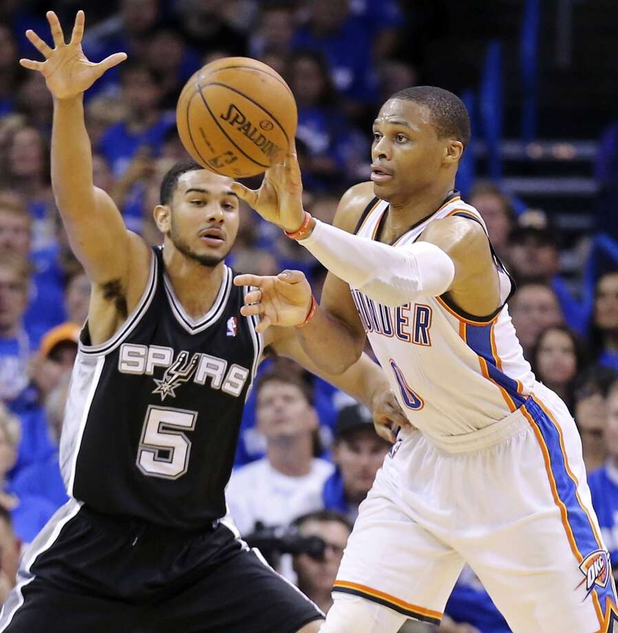 Oklahoma City Thunder's Russell Westbrook passes around San Antonio Spurs' Cory Joseph during second half action in Game 4 of the Western Conference Finals Tuesday May 27, 2014 at Chesapeake Energy Arena in Oklahoma City, OK. Photo: Edward A. Ornelas, San Antonio Express-News