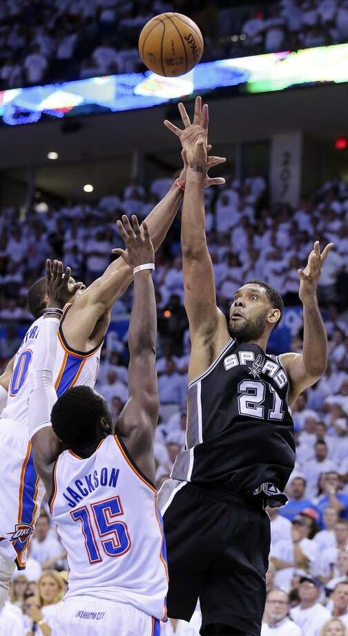 San Antonio Spurs' Tim Duncan shoots over Oklahoma City Thunder's Russell Westbrook (left) and Reggie Jackson during overtime action in Game 6 of the Western Conference finals Saturday May 31, 2014 at Chesapeake Energy Arena in Oklahoma City, OK. The Spurs won 112-107 and advance to the NBA Finals to play the Miami Heat. Photo: Edward A. Ornelas, San Antonio Express-News