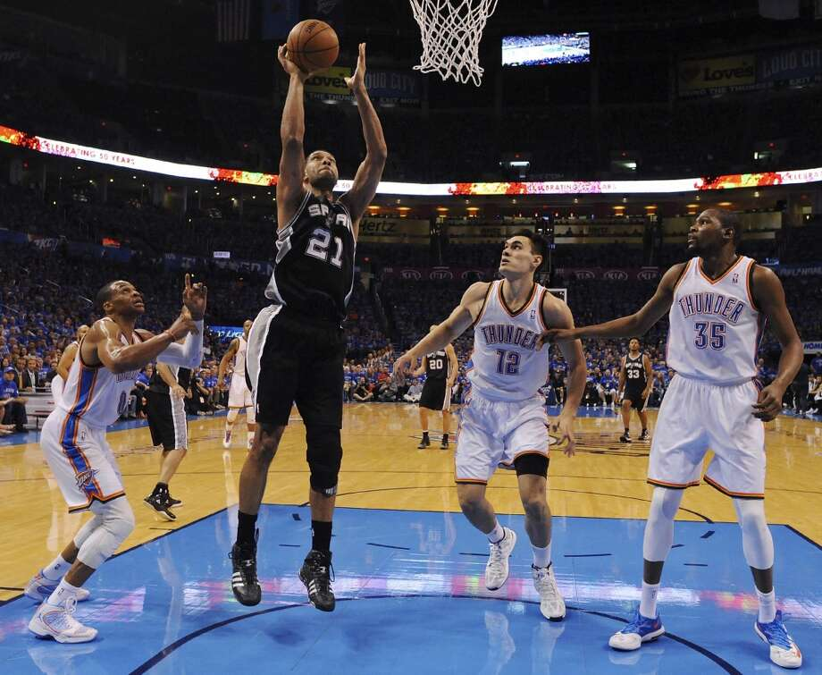 San Antonio Spurs' Tim Duncan shoots between Oklahoma City Thunder's Russell Westbrook (from left), Steven Adams, and Kevin Durant during first half action in Game 3 of the Western Conference Finals Sunday May 25, 2014 at Chesapeake Energy Arena in Oklahoma City, OK. Photo: Edward A. Ornelas, San Antonio Express-News