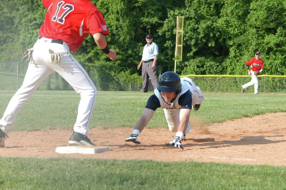 Staples' Sam Ellinwood, right, retreats to first base on a pickoff attempt during Warde's 11-8 win over Staples on Tuesday. Left: Warde's Reece Maniscalco. Photo: Andy Hutchison/For The Westport / Westport News Contributed