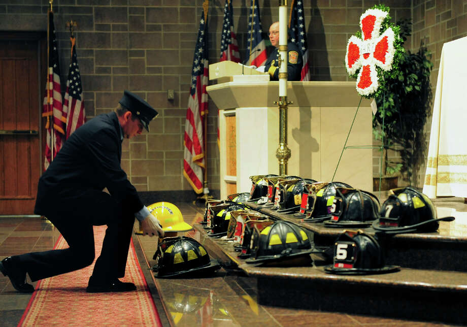 Easton firefighter David Davies places a helment onto the alter in honor of fellow Easton firefighter Lt. Russell Neary, during the Bridgeport Area Retired Firefighters 31st Annual Memorial Service held at St. Catherine of Siena Church in Trumbull, Conn. on Tuesday June 3, 2014. Neary died in the line of duty during Superstorm Sandy on October 29, 2012. Photo: Christian Abraham / Connecticut Post