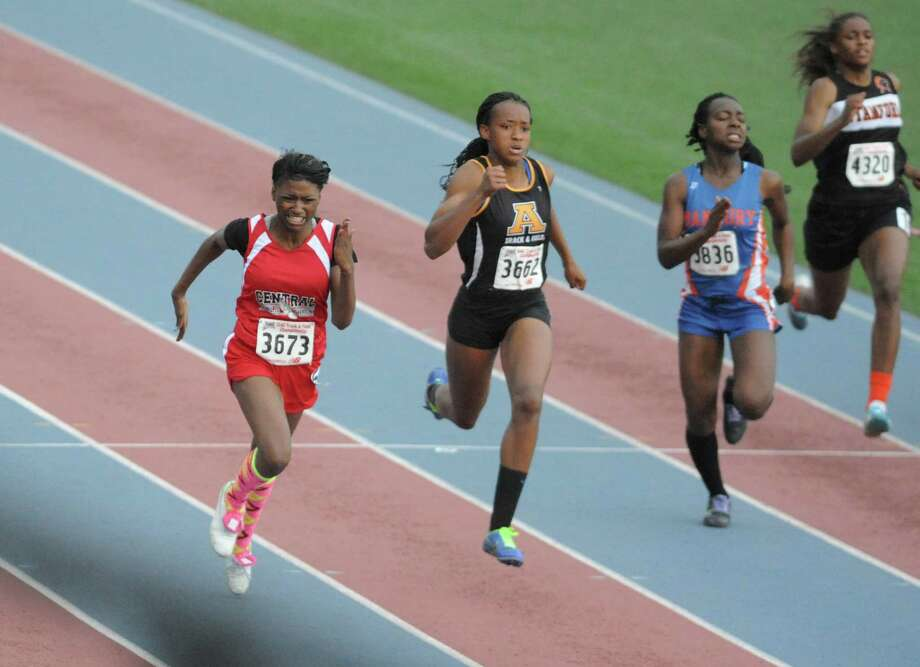 Bridgeport Central's Kanajzae Brown, left, leads Amity's Zoie Reed, center, and Danbury's Niema Riley in the girls 100 meter dash final at the CIAC Class LL Connecticut Outdoor Track & Field State Championship at Danbury High School in Danbury, Conn. Tuesday, June 3, 2014.  Brown won the event with a time of 12.45, with Reed finishing second and Riley finishing third. Photo: Tyler Sizemore / The News-Times
