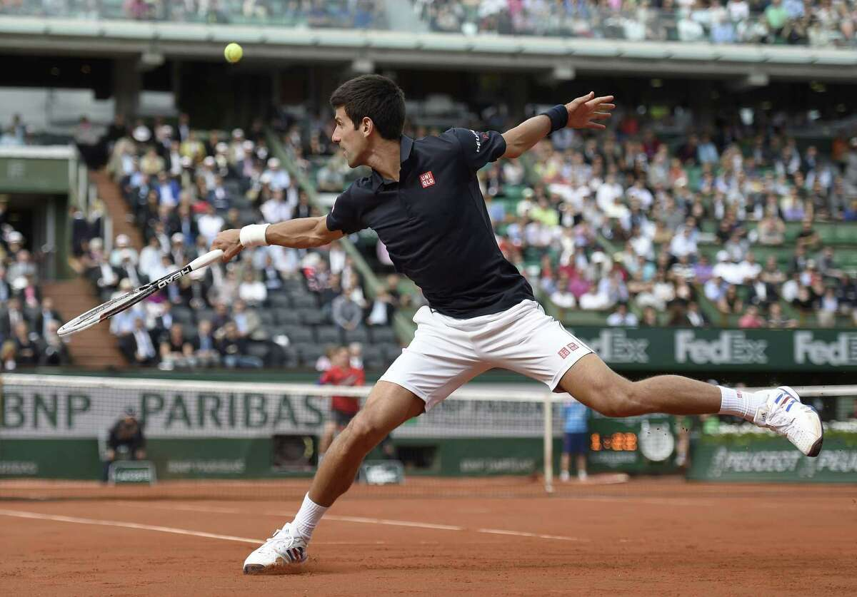Serbia's Novak Djokovic hits a return to Canada's Milos Raonic during their French tennis Open quarter final match at the Roland Garros stadium in Paris on June 3, 2014. AFP PHOTO / PASCAL GUYOTPASCAL GUYOT/AFP/Getty Images ORG XMIT: 492606029