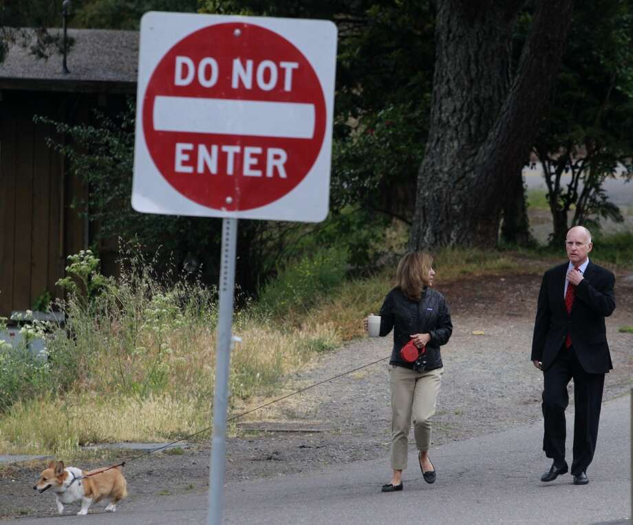 Sutter, California's first dog, leads the way for Gov. Jerry Brown and his wife Anne Gust, as the governor arrives to cast his ballot at a polling place in Oakland, Calif. on Tuesday, June 3, 2014. Brown is running for reelection for a second consecutive term and will likely face either Republicans Neel Kashkari or Tim Donnelly in the November general election. Photo: Paul Chinn, The Chronicle