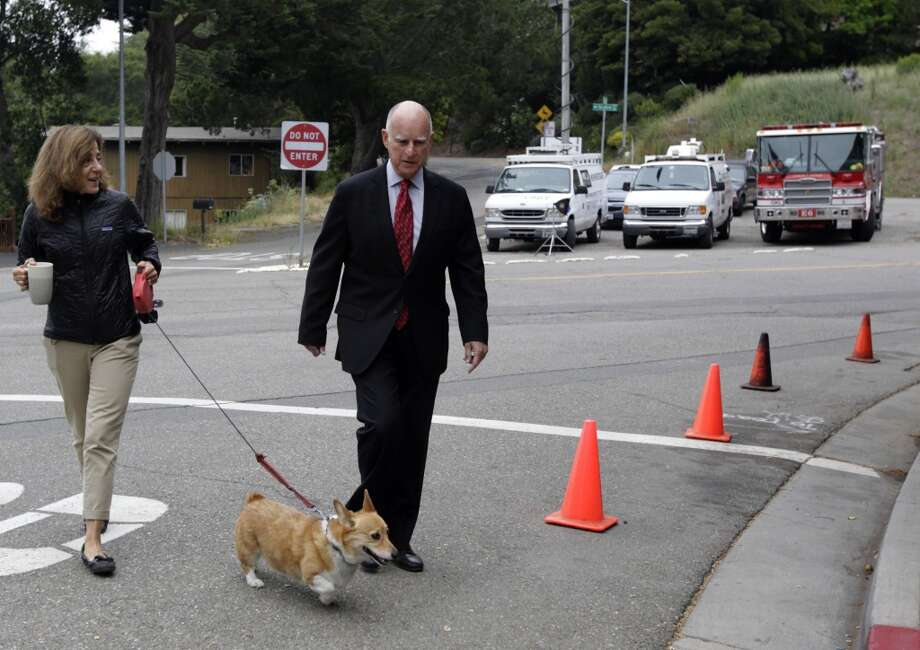 Gov. Jerry Brown arrives at a polling place with his wife Anne Gust and dog Sutter to cast his ballot in Oakland, Calif. on Tuesday, June 3, 2014. Brown is running for reelection for a second consecutive term and will likely face either Republicans Neel Kashkari or Tim Donnelly in the November general election. Photo: Paul Chinn, The Chronicle