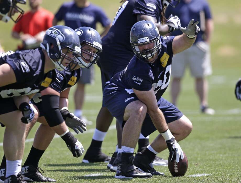 Seattle Seahawks center Max Unger (right) signals to teammates Justin Britt (left) and J.R. Sweezy during Seahawks OTAs. Photo: Elaine Thompson, Associated Press