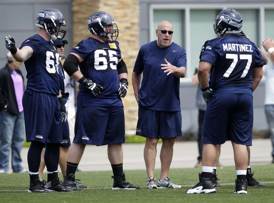 Seahawks offensive line coach Tom Cable, (second from right) talks with Justin Britt (left) Bronson Irwin, (65) and John Martinez (77) during rookie minicamp. Photo: Ted S. Warren, Associated Press