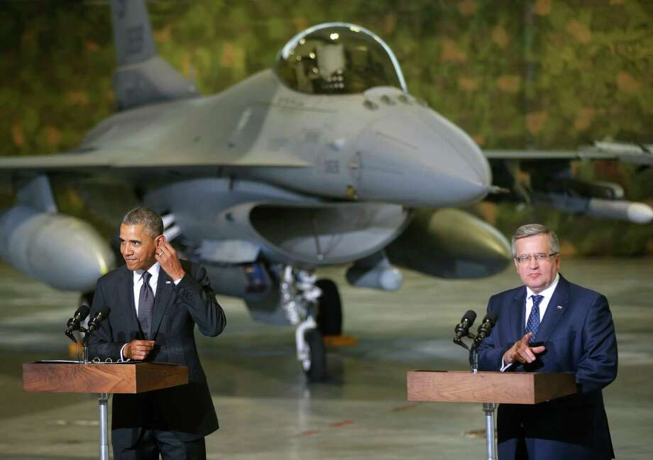U.S. President Barack Obama and Poland's President Bronislaw Komorowski make statements and meet with U.S. and Polish troops at an event featuring four F-16 fighter jets, two American and two Polish, as part of multinational military exercises, in Warsaw, Poland, Tuesday, June 3, 2014. (AP Photo/Charles Dharapak) ORG XMIT: POLD105 Photo: Charles Dharapak / AP