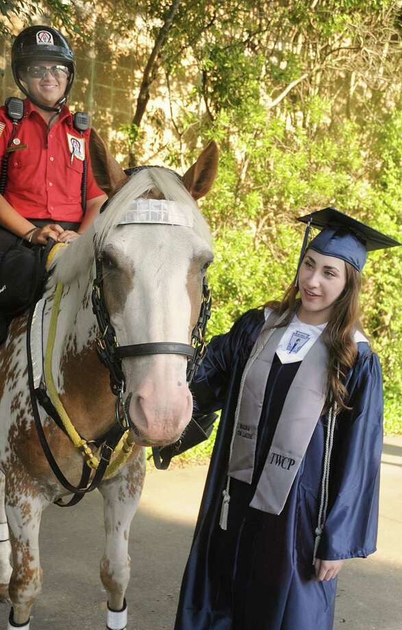 Graduate Alison Bohn pauses to pet Alpha & Omega horse Nitro, ridden by Officer Sofia Bashir, of Spring, during the College Park High School Commencement ceremony at Cynthia Mitchell Pavilion.  Photo: David Hopper, For The Chronicle / freelance