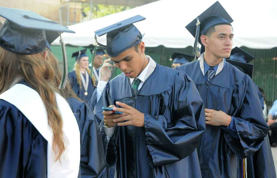 Graduate Mohamed Benali texts his family as he marches into the pavilion during the College Park High School Commencement ceremony at Cynthia Mitchell Pavilion.  Photo: David Hopper, For The Chronicle / freelance