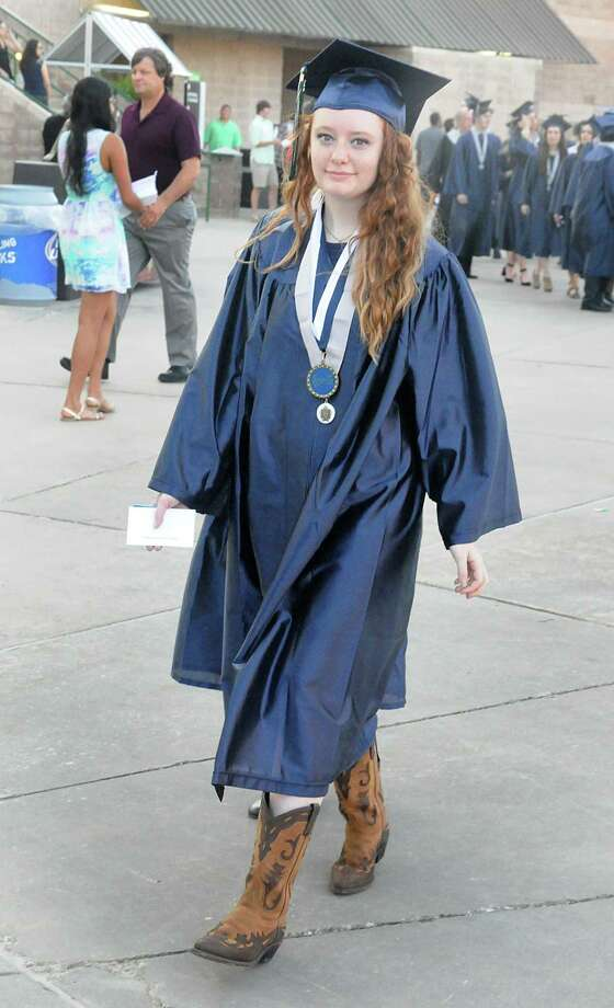 Graduate Ashley Colston wears her boots and gown as she marches into the Pavilion during the College Park High School Commencement ceremony at Cynthia Mitchell Pavilion.  Photo: David Hopper, For The Chronicle / freelance