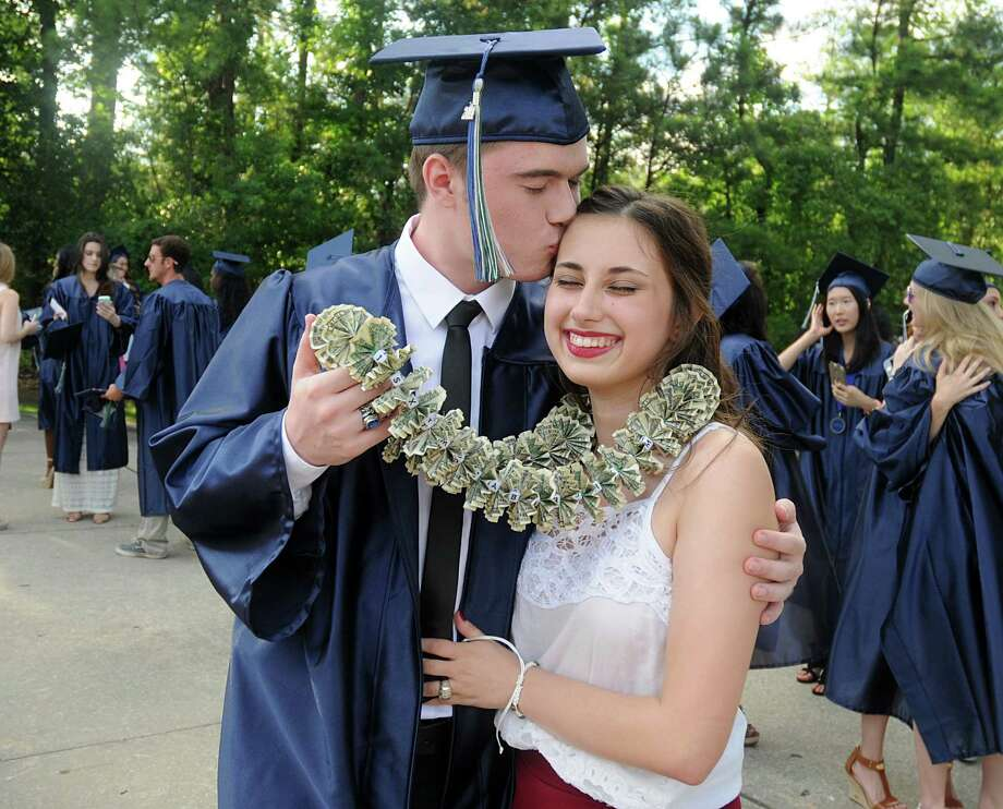 Kiska Sanchez receives a kiss from graduate Tracis Rundell gor his dollar bill lei during the College Park High School Commencement ceremony at Cynthia Mitchell Pavilion.  Photo: David Hopper, For The Chronicle / freelance