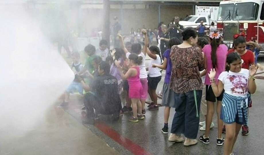 San Antonio firefighters let Frederick Douglass Academy students tour their fire trucks and spray the fire hoses. Photo: Courtesy Photo San Antonio Fire