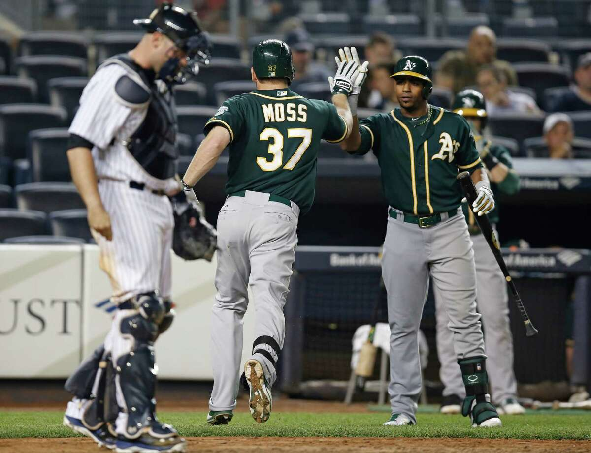 Oakland Athletics on-deck batter Yoenis Cespedes greets Brandon Moss (37) after Moss hit a 10-inning solo home run off New York Yankees relief pitcher Adam Warren in a baseball game at Yankee Stadium in New York, Tuesday, June 3, 2014. Yankees catcher Brian McCann is at left. (AP Photo/Kathy Willens) ORG XMIT: NYY121