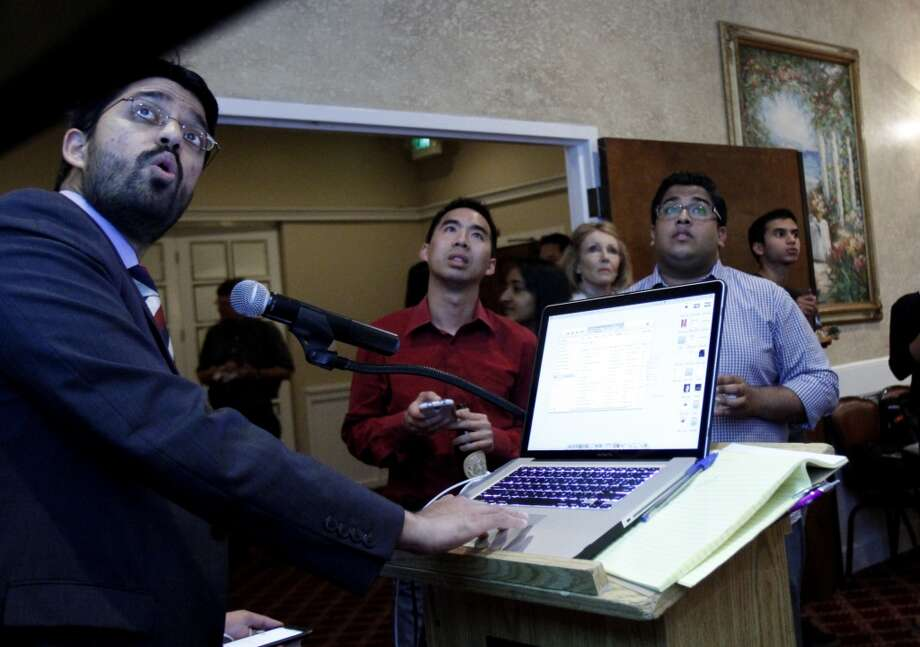 Communications director Vivek Kembaiyan brings up the election results coming in at Congressman Mike Honda's election party at Massimo's in Fremont, Calif., on Tuesday, June 3, 2014.  Watching are Nick Lepham, center, and Vedant Patel, right. Photo: Sarah Rice, Special To The Chronicle