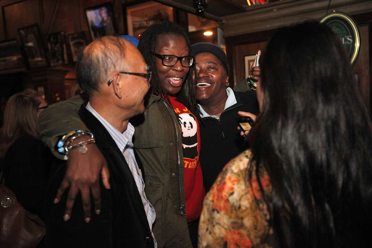 Field director Jackie Omotalade, center, hugs David Chan, with Asian community outreach, left, and volunteer Paul Spicer, right, while chatting with volunteer Lily Cai, far right, as they celebrate election results for David Chiu in the State Assembly primary with other volunteers, friends, family and community members June 3, 2014 at Lefty Doul's in San Francisco, Calif.