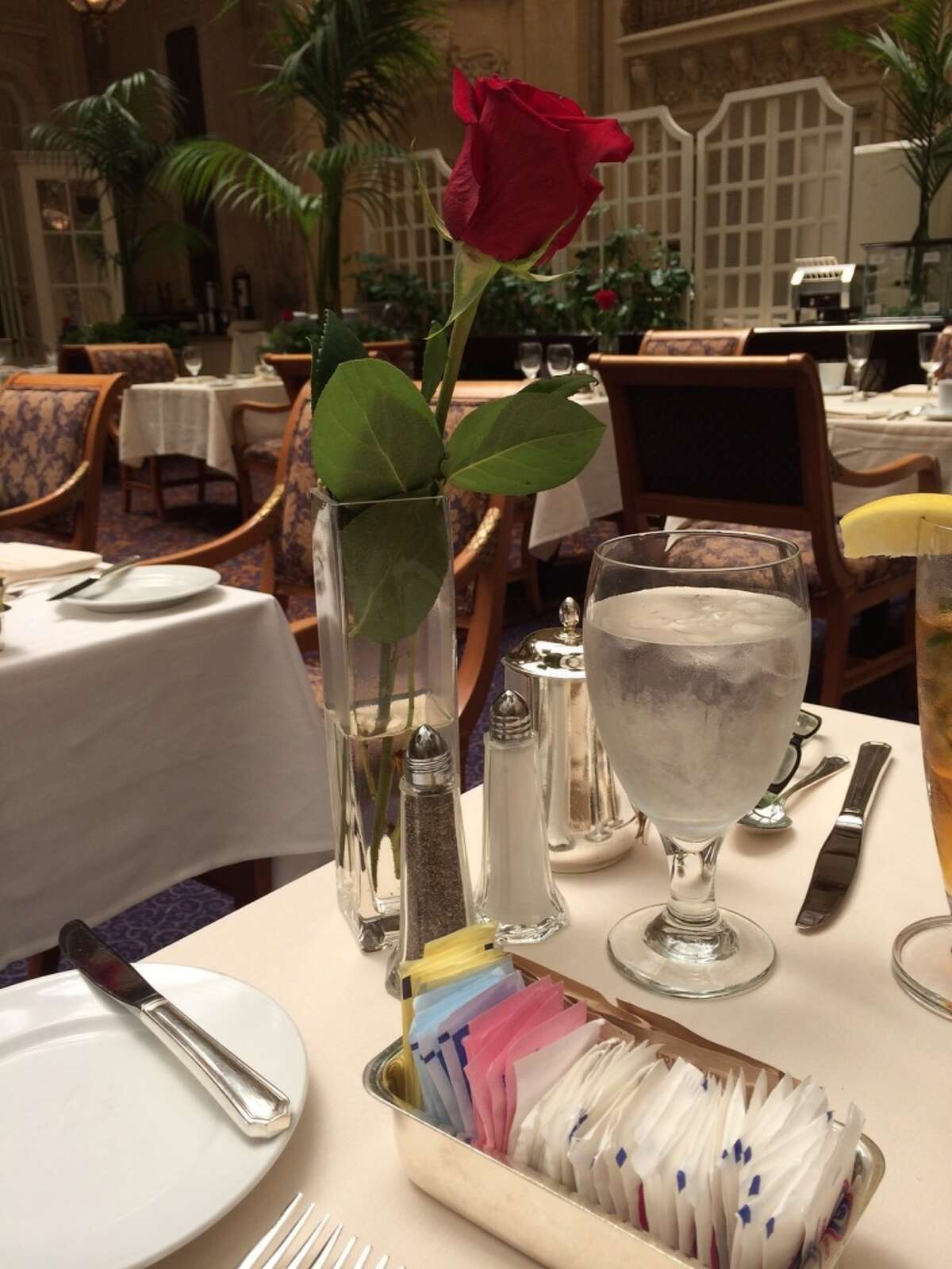 Each table is set with heavy hotel silver and a single red rose.