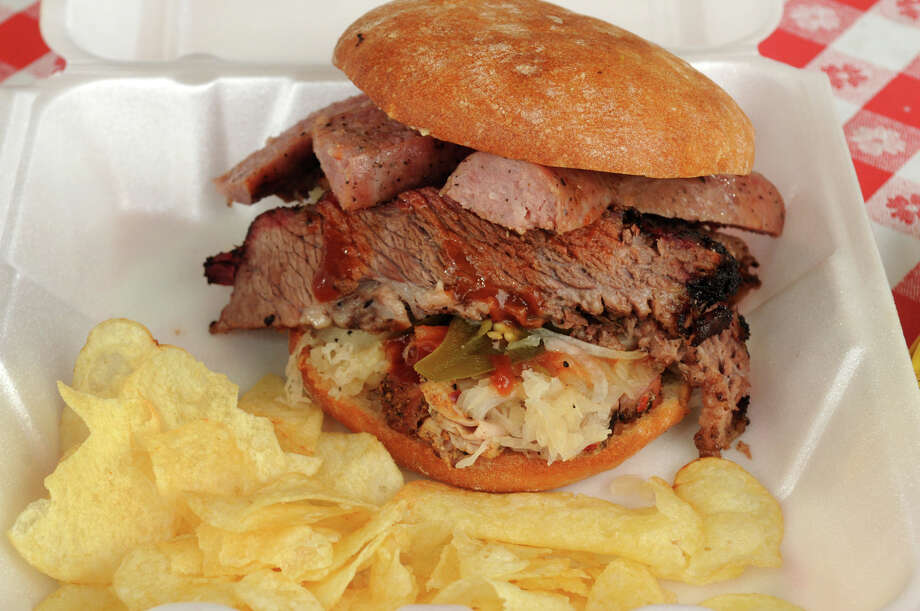 The masterpiece of The Wooden Spoke cuisine in Magnolia is the Big Mike, a 1 1/2 sandwich made with pork loin, barbecue sauce, sausage, jalapeno peppers, onion, sauerkraut, and special sauce all served on a ciabatta bun. Photo: Jerry Baker, Freelance