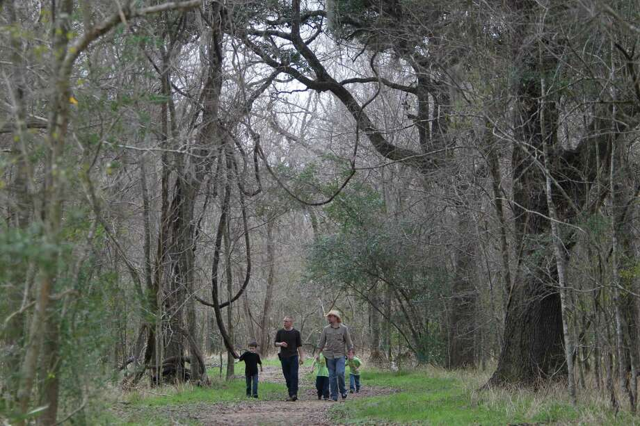 Ryan Falcon, 7, Brett Neiditk, and Derrick Smith hike along Red Buckeye Trail at Brazos Bend State Park which shares a border with Brazos River on Sunday, Jan. 22, 2012, in Needville, TX. ( Mayra Beltran / Houston Chronicle ) Photo: Mayra Beltran, Staff / © 2012 Houston Chronicle