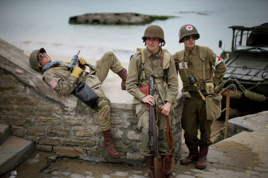 French teenagers who are part of a WWII reenactment group relax on the promenade of Arromanche next to 'Gold Beach'as preparations for the 70th Anniversary Of D-Day are finalised on June 2, 2014 in Arromanches-les-Bains, France. Friday 6th June is the 70th anniversary of the D-Day landings which saw 156,000 troops from the allied countries including the United Kingdom and the United States join forces to launch an audacious attack on the beaches of Normandy,  these assaults are credited with the eventual defeat of Nazi Germany. A series of events commemorating the 70th anniversary are planned for the week with many heads of state traveling to the famous beaches to pay their respects to those who lost their lives. Photo: Christopher Furlong, Getty Images / 2014 Getty Images