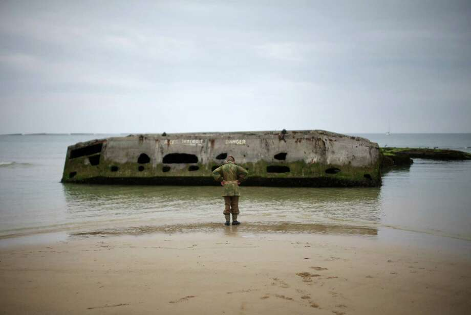 A young boy, who is  part of a WWII reenactment group, walks along 'Gold Beach' and looks at part of a Mulberry pontoon at Arromanche as preparations for the 70th Anniversary Of D-Day are finalised on June 2, 2014 in Arromanches-les-Bains, France. Friday 6th June is the 70th anniversary of the D-Day landings which saw 156,000 troops from the allied countries including the United Kingdom and the United States join forces to launch an audacious attack on the beaches of Normandy,  these assaults are credited with the eventual defeat of Nazi Germany. A series of events commemorating the 70th anniversary are planned for the week with many heads of state traveling to the famous beaches to pay their respects to those who lost their lives. Photo: Christopher Furlong, Getty Images / 2014 Getty Images