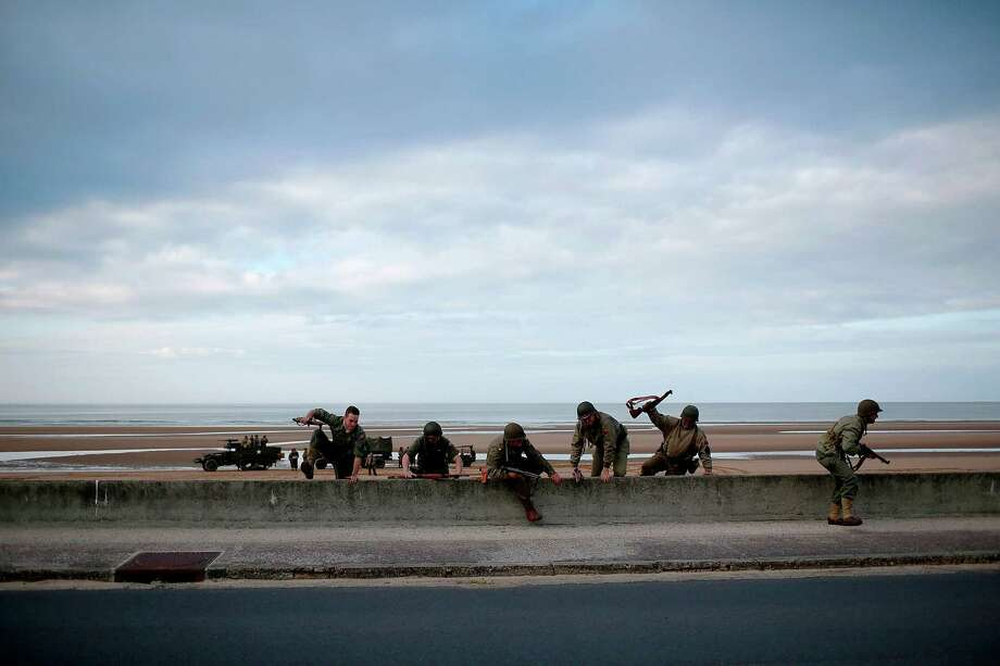 A group of World War II re-enactors from Spain practice scaling a seawall on the Avenue de la Liberation that runs parallel to Omaha Beach June 2, 2014 in Vierville, France. June 6th is the 70th anniversary of the D-Day landings which saw 156,000 troops from the allied countries including the United States and the United Kingdom join forces to launch an attack on the beaches of Normandy, these assaults are credited with the eventual defeat of Nazi Germany. A series of events commemorating the 70th anniversary are planned for the week with many heads of state traveling to the famous beaches to pay their respects to those who lost their lives. Photo: Win McNamee, Getty Images / 2014 Getty Images