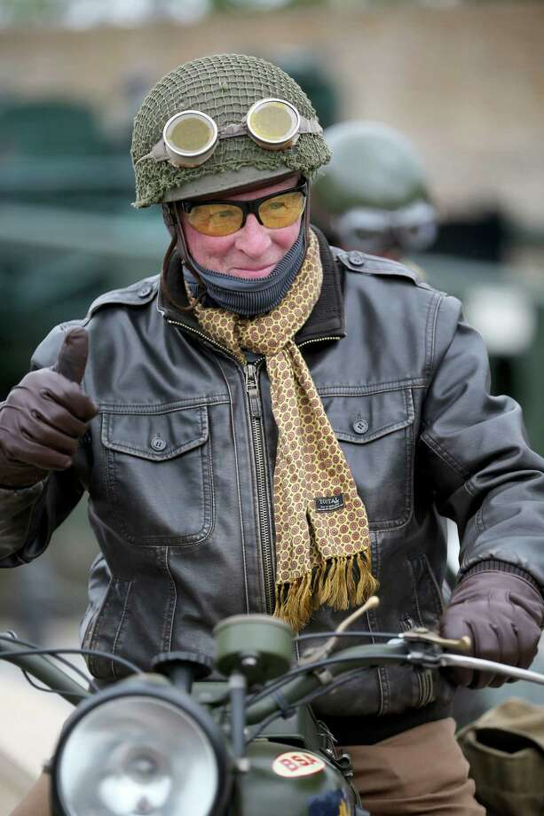 A members of a WWII reenactment group arrives at Arromanches on his motorcycle as preparations for the 70th Anniversary Of D-Day are finalized on June 2, 2014 in Arromanches-les-Bains, France. Friday 6th June is the 70th anniversary of the D-Day landings which saw 156,000 troops from the allied countries including the United Kingdom and the United States join forces to launch an audacious attack on the beaches of Normandy,  these assaults are credited with the eventual defeat of Nazi Germany. A series of events commemorating the 70th anniversary are planned for the week with many heads of state traveling to the famous beaches to pay their respects to those who lost their lives. Photo: Christopher Furlong, Getty Images / 2014 Getty Images